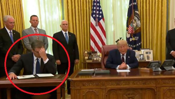 El presidente de Serbia empieza a hojear el acuerdo que acababa de firmar. Luego mira a su derecha, aparentemente a un ayudante de pie, y se toca la frente con lo que parece desconcierto. (Foto: Captura de The White House/YouTube)