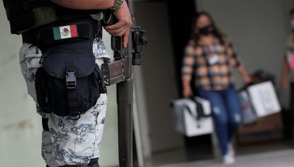Un miembro de la Guardia Nacional monta guardia mientras un trabajador del Instituto Nacional Electoral (INE) lleva material de votación para ser distribuido a los colegios electorales en México (Foto: REUTERS / Daniel Becerril).