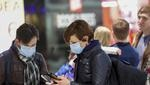 Travelers wear face masks while checking their smartphones at Frankfurt Airport, operated by Fraport AG, in Frankfurt, Germany, on Thursday, March 12, 2020. President Donald Trumps 30-day ban on Europeans traveling to the U.S. delivers a hammer blow to a global airline industry that was already at risk of losing as much as $113 billion in passenger revenue this year because of the coronavirus. Photographer: Alex Kraus/Bloomberg via Getty Images