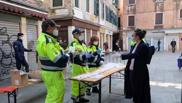 Trabajadores reparten mascarillas en Italia. (Foto: Reuters)
