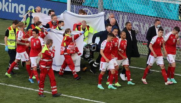 Los seleccionados de Dinamarca y el cuerpo médico protegen a Christian Eriksen. (Foto: EFE)