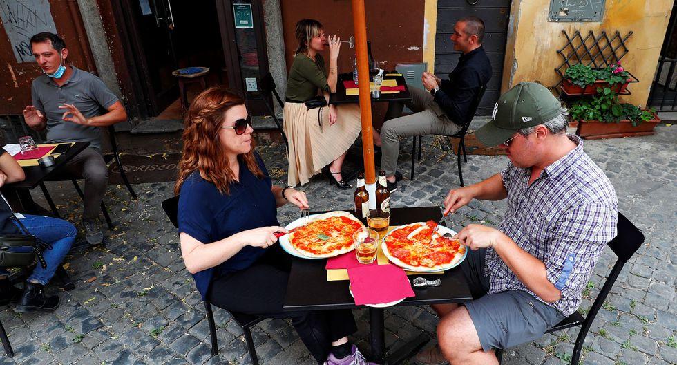 Varias parejas disfrutan de una pizza en un restaurante de Roma. (Foto: Guglielmo Mangiapane / Reuters)