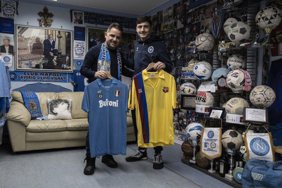 Massimo Vignati (camiseta de Napoli) junto a su hijo (Barcelona) en su museo dedicado a los objetos de Maradona. (Foto: Paolo Manzo / El País)