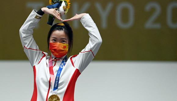 Gold medal winner China's Yang Qian celebrates on the podium after winning the women's 10m air rifle final during the Tokyo 2020 Olympic Games at the Asaka Shooting Range in the Nerima district of Tokyo on July 24, 2021. (Photo by Tauseef MUSTAFA / AFP)