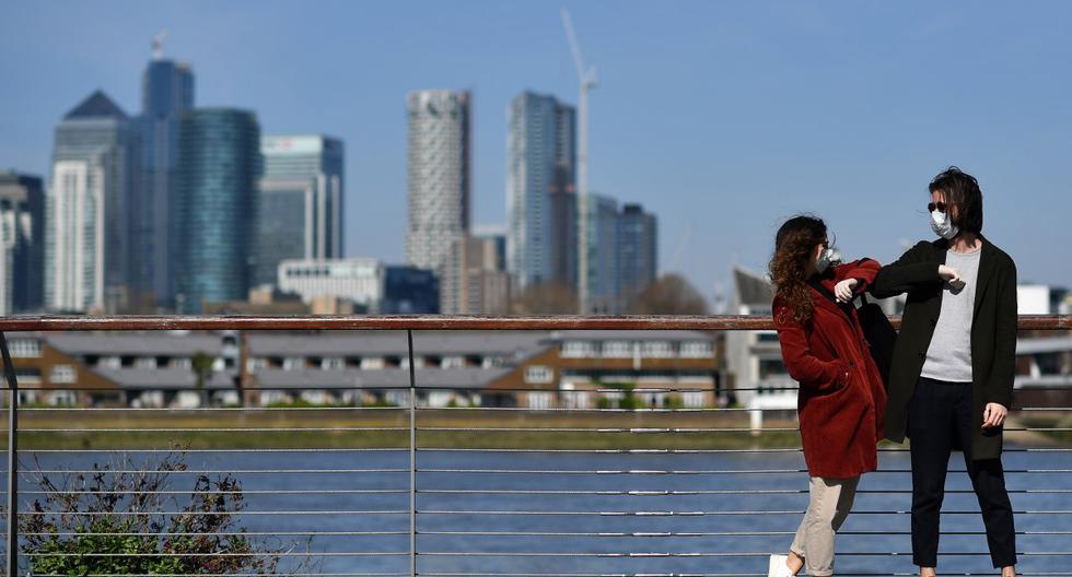 Imagen referencial. Personas con mascarillas se saludan con el codo en Greenwich, en el sur de Londres. (Ben STANSALL / AFP).