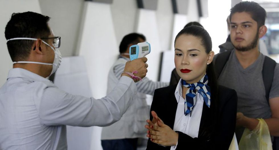 A health worker checks the temperature of passengers as a preventive measure due to the outbreak of the new coronavirus, at the new Central Bus Station in Tlaquepaque, Jalisco state, Mexico, on March 17, 2020. - Mexico's Health Ministry confirmed the country's 83rd case of coronavirus Monday. (Photo by Ulises Ruiz / AFP)